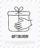 Safety delivery of christmas gift. Hands in protective gloves holding gift box. Christmas in new normal. Thin line icon, vector illustration.