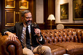 Mature man enjoying a glass of red wine at luxurious apartment