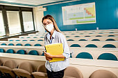 Female student wearing face protective medical mask for virus protection standing at lecture hall