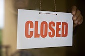 Business store owner turning closed sign at shop doorway