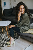 Pretty young woman with curly hair using mobile phone by the window at home
