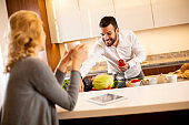 Woman drinking coffee at the kitchen table while man preparing food