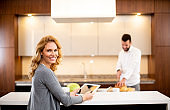 Woman using tablet at the kitchen table while man preparing food