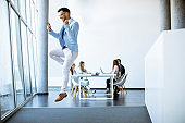 Young businessman with smartphone jumping in a modern office