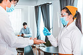 Asian waitress wear protective face mask explain and Using alcohol gel clean wash hand scan customer temperature before entering the restaurant to protect infection from coronavirus, social distancing concept