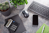 home office desk with keyboard computer smartphone notebook houseplants, workspace at home