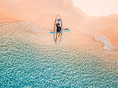 Aerial shot of man relaxing in a kayak Summer seascape beach and blue sea water Top view from drone