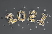 Colors yellow and gray , Color of the year of 2021 Illuminating , Ultimate Gray. Golden Christmas 2021 balloons isolated on red background.