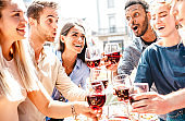 Happy multiracial friends having fun drinking and toasting red wine at lunch party - Young people eating bbq food at restaurant winery together - Dining lifestyle concept on bright warm filter