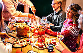 Happy young friends tasting Christmas sweet food having fun at home supper party - Winter friendship concept with millenial people enjoying new year's eve dinner eating together - Warm filter
