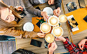 Top view of friends toasting cappuccino at coffee shop restauran