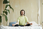 handsome man with long hair meditating on the bed