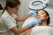 professional cosmetologist working with beautiful woman face in blue gloves at dermatology clinic