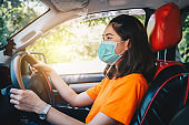 Young Asian woman wearing surgical mask for prevent the spread of coronavirus while driving car.