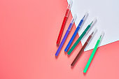 Multi colored felt pens and white blank paper sheet for drawing lies on pink desk in kindergarten. Ð¡oncept of parenting and education of children. Copy space. Top view