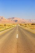 Endless road driving drive empty desert landscape portrait format loneliness infinite