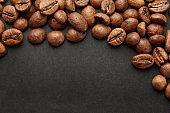 Brown roasted coffee beans on dark background. Espresso dark, aroma, black caffeine drink. Closeup isolated energy mocha, cappuccino ingredient.