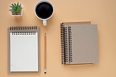 Top view of open school notebook with blank pages and pencil with coffee cup on brown background. Flat lay, creative workspace office. Business or education concept with copy space.