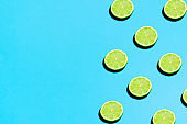 Summer abstract trendy fresh concept. Lime pattern on bright light blue background, copy space. Minimal flat lay food texture