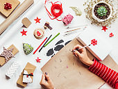 Top view on table with Christmas decorations. Woman draws New Year symbols on craft paper and wraps presents. Festive flat lay background. DIY gifts for winter holiday.