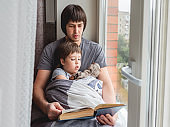 Father reads book to his son. Cozy family time on windowsill while raining outside. Toddler boy sits together with fluffy toy cover himself with a blanket.