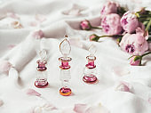Three graceful bottles for perfume or essential oil on white crumpled fabric. Pink glass bottles with eastern ornament. Pink rose bouquet and petals as decoration.