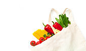Eco bag with vegetables and spaghetti on white background. Ingredients for cooking, concept zero waste. Close-up