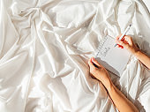 Woman is preparing to write list of her goals. Top view on crumpled bed sheet and notepad with white paper pages. Practice of positive writing at morning after waking up. Flat lay with copy space.