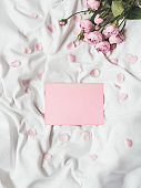 Roses and petals on crumpled white fabric. Natural elegant decoration. Romantic background with copy space on pink envelope. Top view, flat lay.