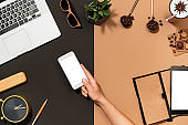 Top view office desk mockup and human hand flat lay