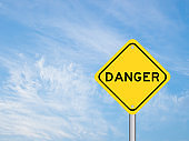 Yellow transportation sign with word danger on blue sky background