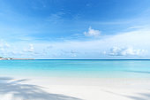Tropical beach and turquoise sea with blue sky background