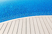 Empty wooden terrace with blue swimming pool copy space scene