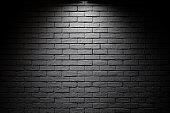 Bright spotlight illuminate dark brick wall