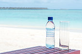 Bottle of mineral water and glass on the beach table