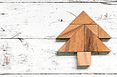 Tangram puzzle in pine or christmas tree shape on old white wood background