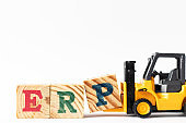 Toy forklift hold wood letter block P to complete word ERP (Abbreviation of Enterprise Resource Planning) on white background