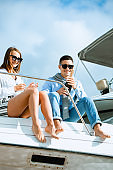 Man uncorking champagne and having party with wife on deck.