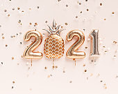 Happy New year 2021 invitation template. Gold foil balloons numeral 2021 and confetti on pastel background. 3d rendering