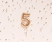 Five year birthday. Number 5 flying foil balloon and confetti. Five-year anniversary background. 3D rendering
