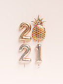 New year 2021 celebration. Gold foil balloons numeral 2021 and cute golden textured pineapple creatuve funny background. 3D rendering