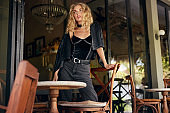 Woman Portrait. Beautiful Blonde Model In Fashionable Clothes. Sexy Female Resting Near Table And Chair In Cafe. Relaxation In Comfortable Restaurant.