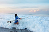 Surfer Girl. Surfing Woman With Surfboard Going To Surf In Ocean. Brunette In Blue Wetsuit Walking Into Splashing Sea. Water Sport For Active Lifestyle.