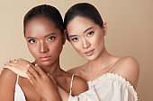 Diverse. Women Beauty Portrait. Multi-Ethnic Models With Natural Makeup And Perfect Skin Against Beige Background. Mixed Race And Asian Girls Standing Together, Hug Each Other And Looking At Camera.