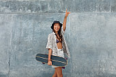 Skater Girl With Skateboard Portrait. Asian Teenager In Casual Outfit Posing Against Concrete Wall At Skatepark. Urban Subculture And Skateboarding As Lifestyle Of Active Teens In City.