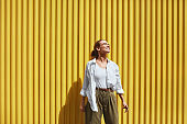 Girl. Portrait Of Stylish Woman. Fashion Model In Casual Clothes And Glasses Standing Against Yellow Metal Fence. Female In White Shirt And Top Tank. Urban Lifestyle.