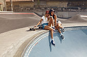 Portrait Of Skater Girls At Skatepark. Female Teenagers In Casual Outfit Sitting On Concrete Ramp. Summer Skateboarding With Modern Sport Equipment As Part Of Active Lifestyle.