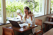 Work. Confused Woman At Coffee Shop. Beautiful Girl In Casual Clothes With Laptop And Headphones Having Online Meeting. Digital Technologies For Comfortable Life On Vacation And Successful Business.