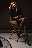 High Fashion Sexy Woman. Erotic Beauty Portrait Of Model On Chair. Seductive Look In Stockings And Jacket.