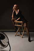 High Fashion Sexy Woman. Erotic Portrait Of Beautiful Model On Chair. Seductive Look In Stockings And Jacket.